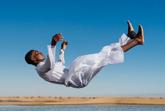Man wearing white clothes falling into a lake